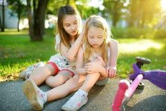 Aanbiddelijk meisje die haar troosten weinig zuster nadat zij van haar autoped bij de zomerpark viel Kind die gekwetst terwijl he stock foto's