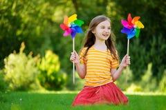 Aanbiddelijk meisje die kleurrijk stuk speelgoed vuurrad op de zomerdag houden Stock Foto