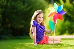 Aanbiddelijk meisje die kleurrijk stuk speelgoed vuurrad op zonnige de zomerdag houden Stock Afbeelding