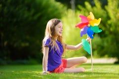 Aanbiddelijk meisje die kleurrijk stuk speelgoed vuurrad op zonnige de zomerdag houden Stock Foto's
