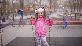Aanbiddelijk meisje die op schommeling in de lentepark slingeren stock video