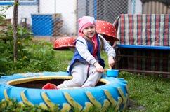 Aanbiddelijk meisje die pret het spelen in openlucht op de zomerdag hebben Royalty-vrije Stock Foto's