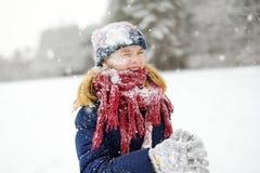 Aanbiddelijk meisje die pret in mooi de winterpark hebben Het leuke kind spelen in een sneeuw stock afbeeldingen