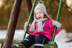 Aanbiddelijk meisje die pret op een schommeling op de winterdag hebben Royalty-vrije Stock Foto's