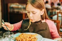 Aanbiddelijk meisje die spaghetti met bolognese saus eten stock foto