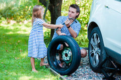 Aanbiddelijk meisje die vader helpen om een autowiel op mooie de zomerdag in openlucht te veranderen Stock Fotografie