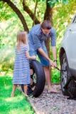 Aanbiddelijk meisje die vader helpen om een autowiel op mooie de zomerdag in openlucht te veranderen Stock Foto