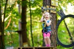 Aanbiddelijk meisje die van haar tijd in het beklimmen van avonturenpark genieten op warme en zonnige de zomerdag royalty-vrije stock foto