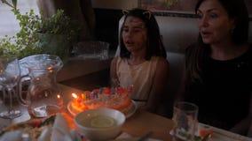 Aanbiddelijk meisje die verjaardagspartij hebben die thuis, kaarsen op verjaardagscake blazen De partij van de jonge geitjesverja stock video