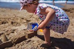 Aanbiddelijk meisje die zandkasteel maken bij strand stock foto's