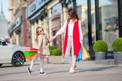Aanbiddelijk meisje en gelukkige moeder die met het winkelen zakken in Europa in openlucht lopen royalty-vrije stock foto's