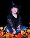 Aanbiddelijk meisje in heksenkostuum met bladeren Stock Foto's