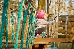 Aanbiddelijk meisje in helm in kabelpark in bos stock foto's