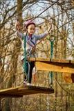 Aanbiddelijk meisje in helm in kabelpark in bos stock afbeelding