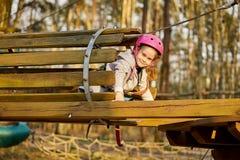 Aanbiddelijk meisje in helm in kabelpark in bos royalty-vrije stock foto's