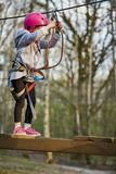 Aanbiddelijk meisje in helm in kabelpark in bos stock fotografie