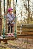 Aanbiddelijk meisje in helm in kabelpark in bos royalty-vrije stock afbeelding