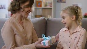 Aanbiddelijk meisje het verrassen mamma met heden, die haar gelukwensen op Moederdag stock video