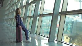 Aanbiddelijk meisje in luchthaven dichtbij het grote venster spelen met haar telefoon stock footage