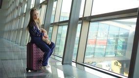Aanbiddelijk meisje met bagage in op het inschepen wachten en luchthaven die uit het venster kijken stock videobeelden