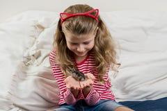 Aanbiddelijk meisje met haar huisdier - kleine hamster stock fotografie