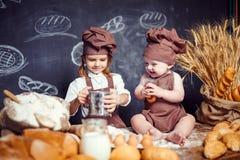 Aanbiddelijk meisje met kind bij lijst het koken Royalty-vrije Stock Foto