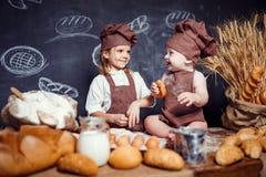 Aanbiddelijk meisje met kind bij lijst het koken Stock Foto