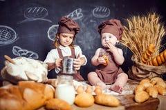 Aanbiddelijk meisje met kind bij lijst het koken Royalty-vrije Stock Afbeelding