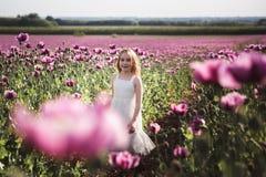 Aanbiddelijk meisje met lang haar in het witte kleding eenzame lopen op het Lilac Poppy Flowers-gebied royalty-vrije stock afbeeldingen