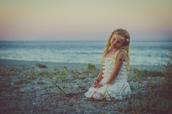 Aanbiddelijk meisje met lange blonde haarzitting alleen in het strand Royalty-vrije Stock Foto's