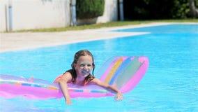Aanbiddelijk meisje met opblaasbare matras in openlucht zwembad stock video