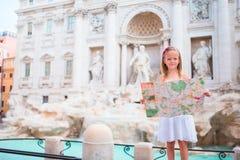 Aanbiddelijk meisje met toeristische kaart dichtbij Trevi Fontein, Rome Het gelukkige jonge geitje geniet van Italiaanse vakantie Stock Afbeelding