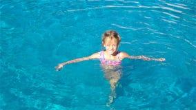 Aanbiddelijk meisje in openlucht zwembad stock video