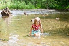 Aanbiddelijk meisje in rivier op zonnige dag Stock Afbeelding
