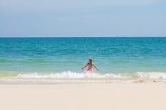 Aanbiddelijk meisje in roze zwemmend die kostuum aan oceaan golven wordt doorgenomen Royalty-vrije Stock Foto's