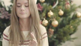 Aanbiddelijk meisje in witte gebreide sweaterzitting tegen verfraaide Kerstmisboom stock videobeelden