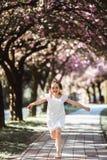 Aanbiddelijk meisje in witte kleding in bloeiende roze tuin op mooie de lentedag stock afbeeldingen