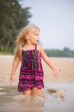 Aanbiddelijk meisjesspel met nat zand op zonsondergang oceaanstrand Stock Afbeeldingen