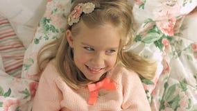 Aanbiddelijk op het bed liggen en meisje die gaily lachen Stock Fotografie