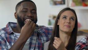 Aanbiddelijk paar die pret het letten op komediefilm hebben en het eten van popcorn, vrije tijd stock video