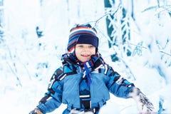 Aanbiddelijk peuterkind die pret met sneeuw hebben in openlucht royalty-vrije stock afbeeldingen
