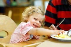 Aanbiddelijk peutermeisje die gezonde groenten en ongezonde frietenaardappels eten Leuk gelukkig babykind die voedsel nemen royalty-vrije stock foto