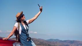 Aanbiddelijk positief ontspannen toeristenwijfje die selfie op auto nemen die smartphone gebruiken stock videobeelden