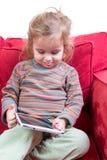 Aanbiddelijk schuw meisje met een tablet-PC Royalty-vrije Stock Foto's