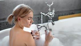 Aanbiddelijk sexy wijfje die douche met masker op de mening van de gezichts achterkant nemen stock footage