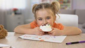 Aanbiddelijk vrouwelijk kind die zoete de zittingslijst van de roomcake, kinderjarengeluk eten stock footage