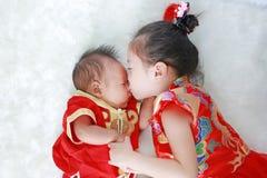 Aanbiddelijk weinig Aziatische de babyjongen van de meisjes kussende zuigeling in cheongsam die op witte bontachtergrond tijdens  royalty-vrije stock foto's