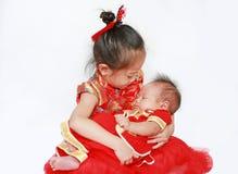 Aanbiddelijk weinig Aziatische die meisje en zuigelingsbabyjongen in cheongsam op witte achtergrond tijdens traditioneel Chinees  royalty-vrije stock fotografie