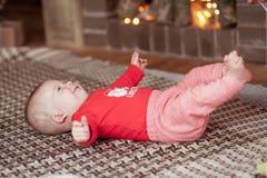 Aanbiddelijk weinig baby die op bed met open haard op achtergrond plaing royalty-vrije stock foto's