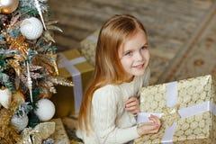 Aanbiddelijk weinig blond meisje met blauwe ogen die en a glimlachen houden Royalty-vrije Stock Foto
